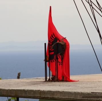 ALBANISCHE FLAGGE AUF EINEM BETONROHBAU IN SARANDA